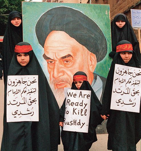 "Young pro-iranian hizbullah girls demontrate in Beirut's shiite southern suburbs 26 February against indian-born british author Salman Rushdie's allegedly blasphemous book ""The satanic verses"". Behind is seen a poster for Iranian Iman Khomeiny who decided to execute Rushdie. CREDIT : NABIL ISMAIL/AFP ImageForum"